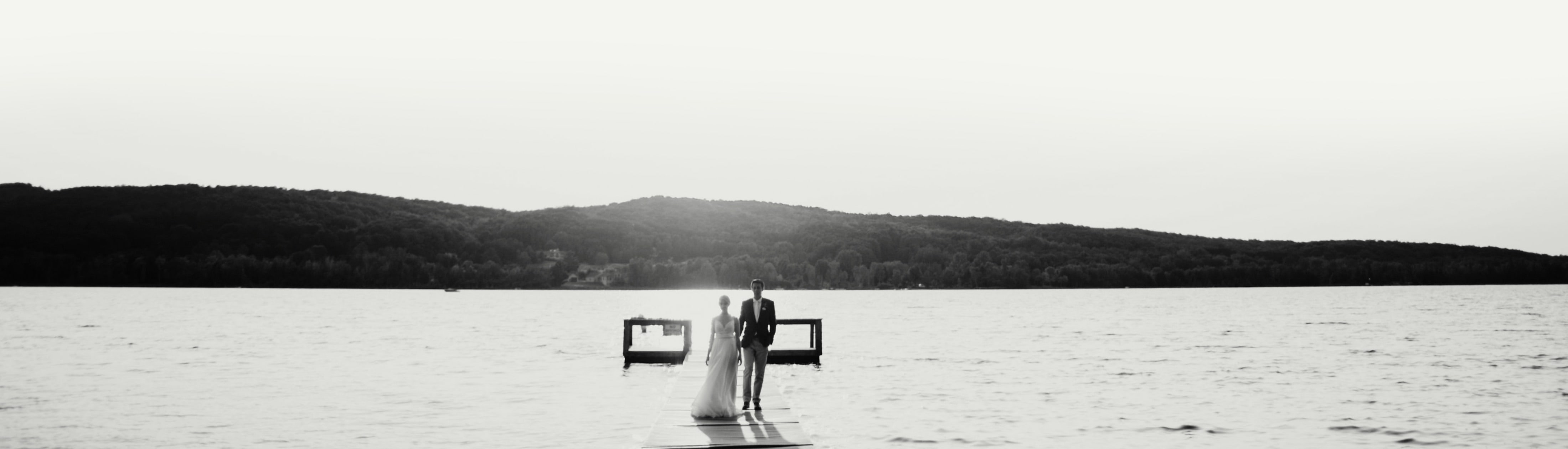 A Bride and Groom standing in front of Deer Lake